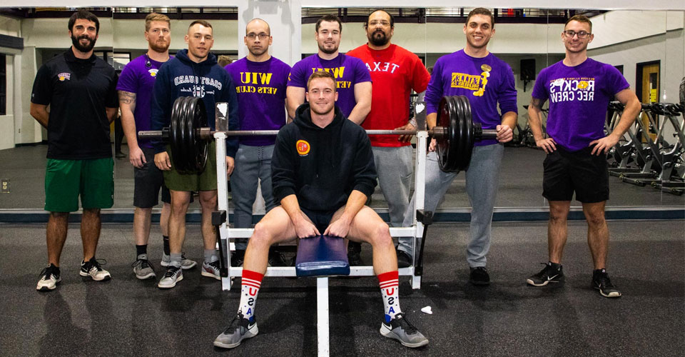 Photo of people posed in a weight room from the 老兵 Club vs ROTC Military Appreciation Week Competitions